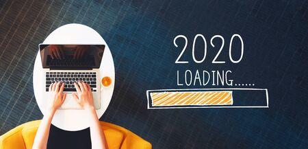Caricamento del nuovo anno 2020 con una persona che utilizza un laptop su un tavolo bianco