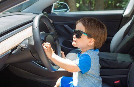 Kleinkindjunge beim Spielen auf dem Fahrersitz seines Familienautos mit Sonnenbrille Standard-Bild