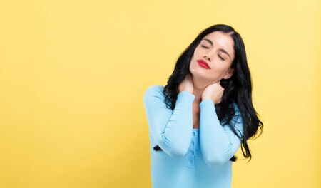 Young woman suffering from headache on a yellow background Stock Photo