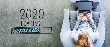 Caricamento del nuovo anno 2020 con un uomo che utilizza un laptop su una moderna sedia grigia