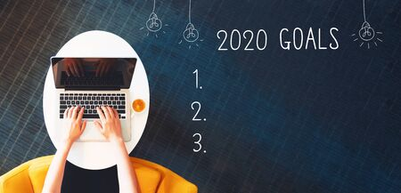 2020 goals with person using a laptop on a white table 스톡 콘텐츠