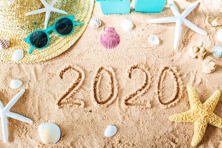 2020 text in the sand with beach accessories Stock Photo