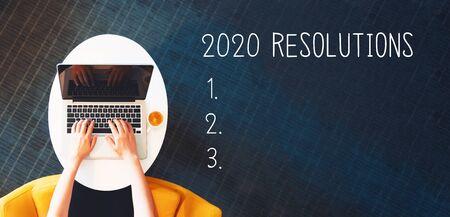 2020 Resolutions with person using a laptop on a white table Foto de archivo