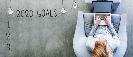 Objetivos 2020 con el hombre usando una computadora portátil en una silla gris moderna