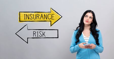 Insurance or risk with thoughtful young woman holding a smartphone Banco de Imagens
