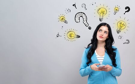 Question with light bulbs with thoughtful young woman holding a smartphone Stock Photo