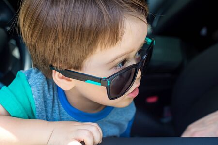 Toddler boy in playing in the driverss seat of his familys car in sunglasses