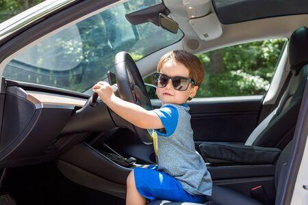 Kleinkindjunge beim Spielen auf dem Fahrersitz seines Familienautos mit Sonnenbrille