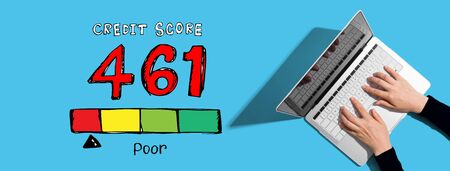 Poor credit score theme with person using a laptop computer