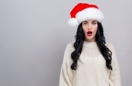 Surprised young woman in a Santa hat on a gray background