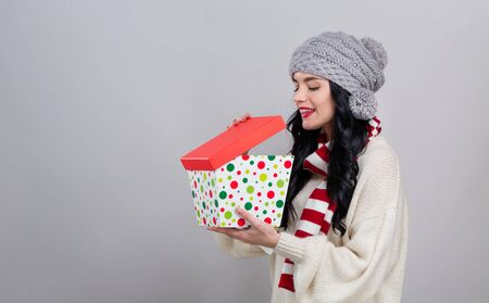 Young woman opening a Christmas present box on a gray background