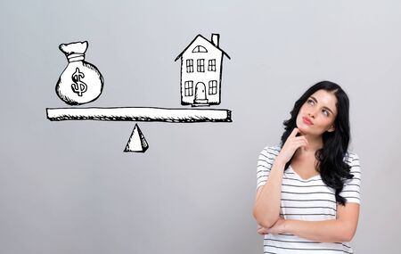 House and money on the scale with young woman in a thoughtful face
