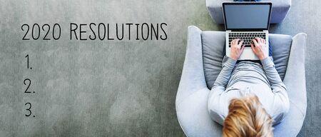 Resoluciones de 2020 con el hombre usando una computadora portátil en una silla gris moderna Foto de archivo