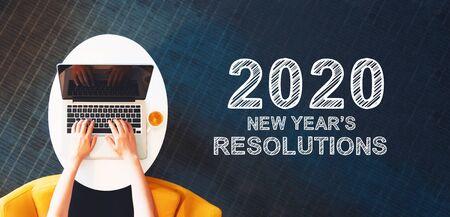 Resoluciones de año nuevo 2020 con persona usando una computadora portátil en una mesa blanca Foto de archivo