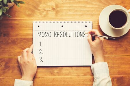 2020 Resolutions with a person holding a pen on a wooden desk
