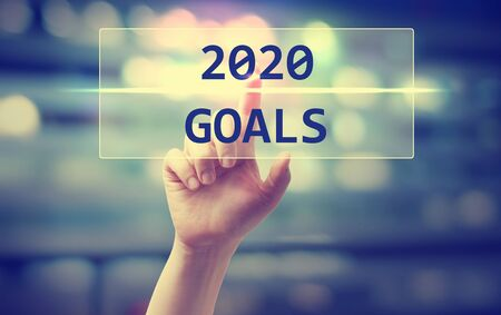 Concepto de objetivos de 2020 con la mano presionando un botón en abstracto borroso