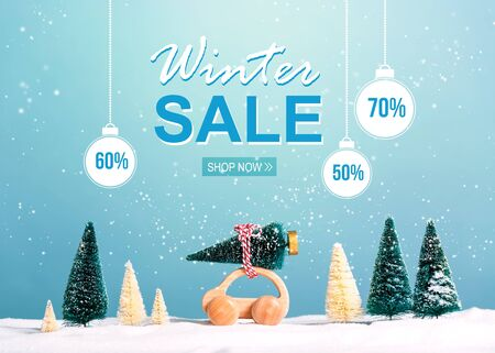 Winter sale message with little car carrying a Christmas tree Stock Photo