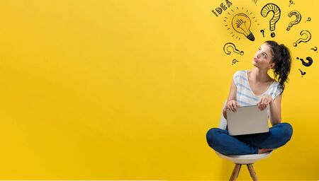 Idea light bulbs with question marks with young woman using a laptop computer Stock Photo