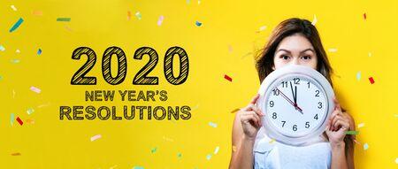 Resoluciones de Año Nuevo de 2020 con una mujer joven que sostiene un reloj que muestra casi 12