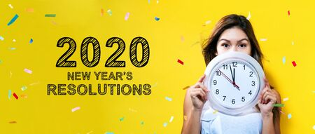 Risoluzioni del nuovo anno 2020 con una giovane donna che tiene in mano un orologio che mostra quasi 12