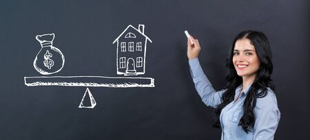 House and money on the scale with young woman writing on a blackboard