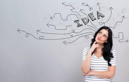 Frecce di idee di brainstorming con una giovane donna in una faccia pensierosa
