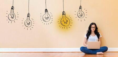 Idea light bulbs with young woman using a laptop computer Фото со стока