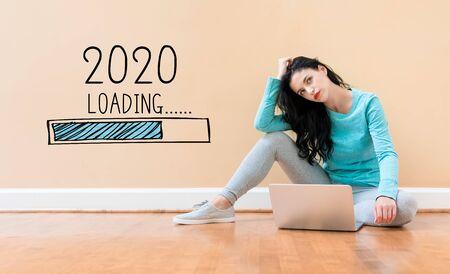 Laden des neuen Jahres 2020 mit junger Frau, die einen Laptop verwendet Standard-Bild