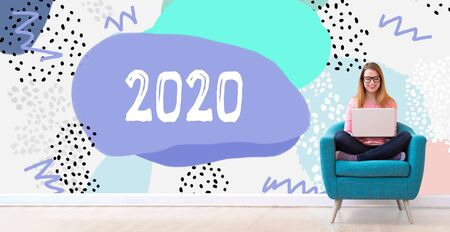 2020 new year concept with young woman using her laptop in a chair