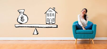 House and money on the scale with woman in a thoughtful pose in a chair