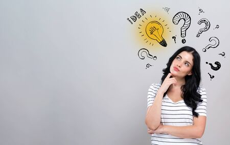 Idea light bulbs and question marks with young woman in a thoughtful face