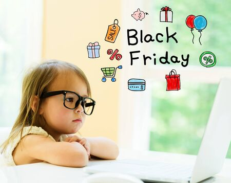 Black Friday text with little girl using her laptop Stock fotó