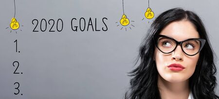 Objetivos 2020 con joven empresaria con rostro pensativo Foto de archivo