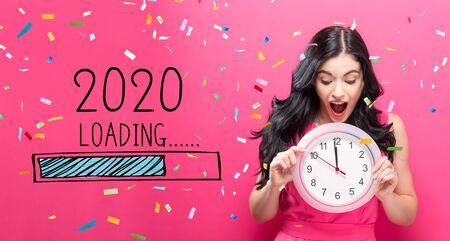 Chargement du nouvel an 2020 avec une jeune femme tenant une horloge indiquant près de 12 Banque d'images