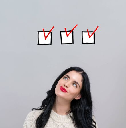 Checklist with happy young woman on a gray background