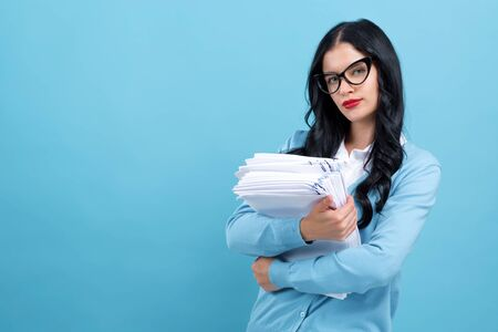 Young woman with a stack of documents on a blue background Reklamní fotografie