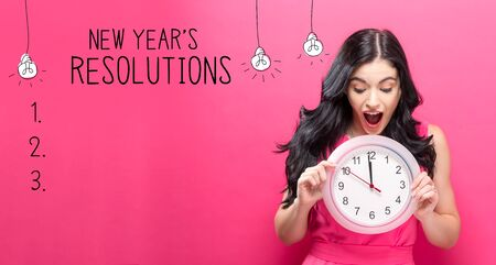 New years resolution with young woman holding a clock showing nearly 12