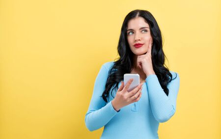 Happy young woman with smart phone thinking about something on a yellow background