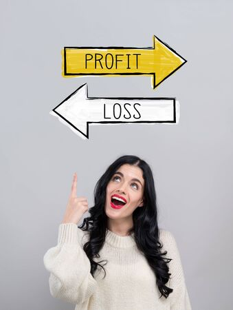 Profit or loss with happy young woman on a gray background