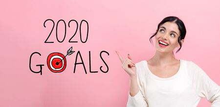 2020 goals concept with happy young woman pointing
