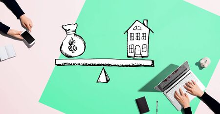 House and money on the scale with people working together with laptop and phone Stock Photo