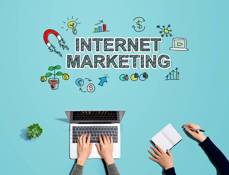 Internet marketing with people working together with laptop and notebook Stock Photo