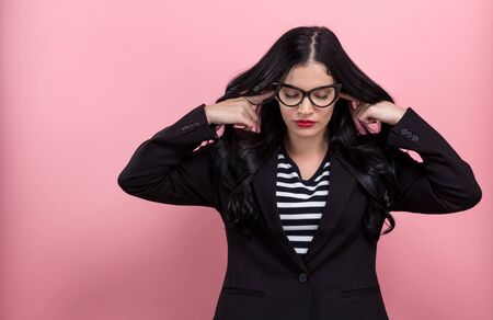 Young woman blocking her ears on a pink background