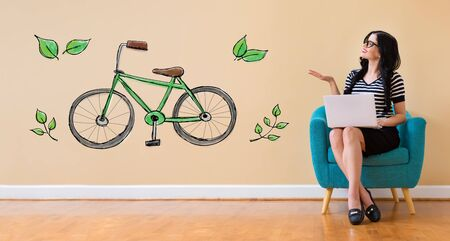 Eco bicycle with young woman using a laptop computer