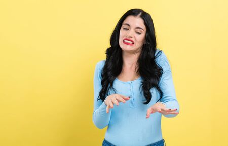 Scared young woman on a yellow background Stockfoto