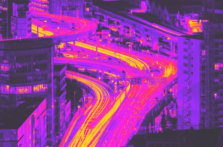Aerial view of a highway interesection in Minato, Tokyo, Japan at night synth wave style Фото со стока