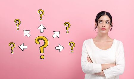 Big and small question marks with arrows with young woman in thoughtful pose Stock Photo