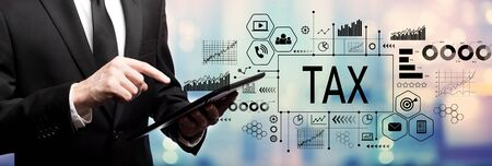 Tax theme with businessman using his tablet computer