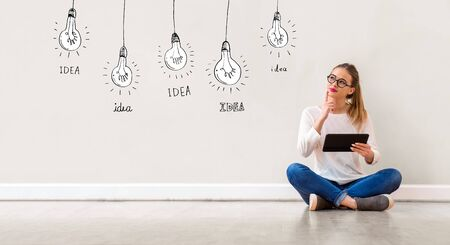 Idea light bulbs with young woman holding a tablet computer Фото со стока - 135492536