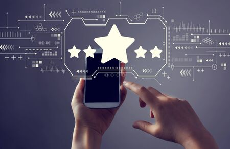 Five star rating with person holding a white smartphone Reklamní fotografie - 135492548